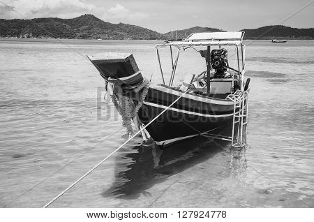 Single touristic boat at Koh Samui, Thailand with sea and mountains. Black and white