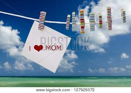 White note with word hang on the rope with wooden peg under blue sky.Mother's Day concept.