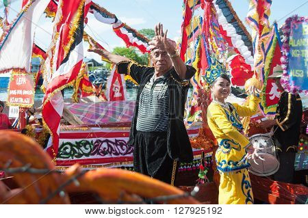 Semporna Sabah Malaysia - Apr 22 2016 : Bajau ethnic man and lady dancing on traditional Bajau's boat called Lepa Lepa decorated with colorfull Sambulayang sail parading during annual Regatta Lepa Festival in Semporna Sabah.