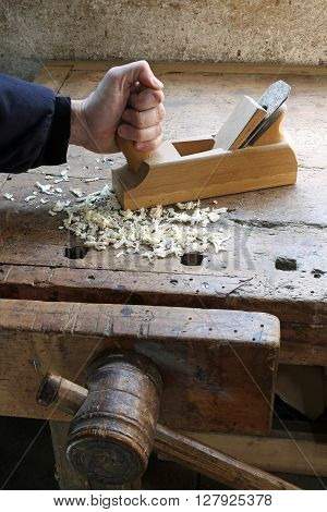Carpenter's Hand In The Carpentry Workshop With A Plane