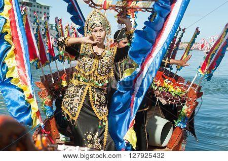 Semporna Sabah Malaysia - Apr 22 2016 : Traditional Bajau's boat called Lepa Lepa decorated with colorfull Sambulayang sail parading during annual Regatta Lepa Festival in Semporna Sabah. 2016 : Bajau lady dancing on traditional boat called Lepa Lepa deco
