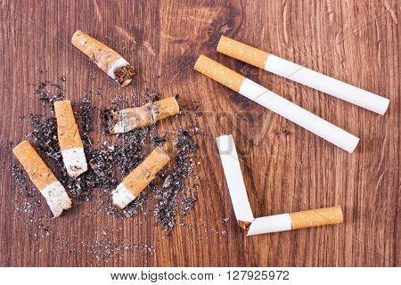 Cigarette butts ash and cigarette on wooden background concept of healthy lifestyles without cigarettes world no tobacco day