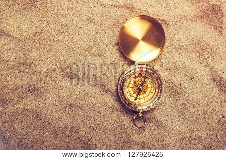 Top view of vintage compass on sandy beach navigational equipment in warm brown sand of summer holiday vacation resort pointing to south.