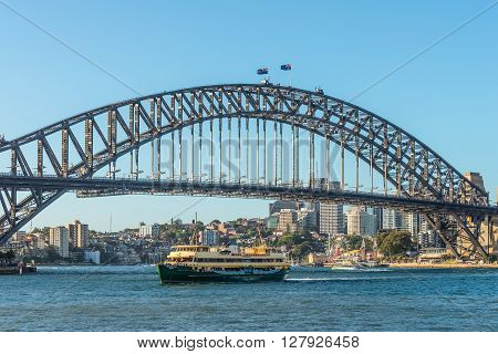 Sydney Australia - November 8 2014: View of the world famous Sydney (Australia) Harbour Bridge Freshwater ferry sailing past and group of people doing bridge climb. Sydney famous Luna Park in the background.