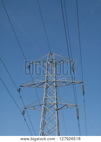 Electricity supply pylon and cables set against a blue sky