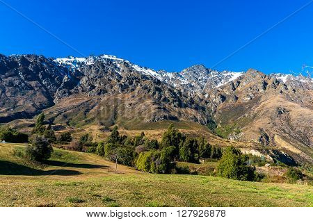 Mountain valley view. Nature landscape background photo of snow covered mountains and green grass Otago New Zealand. Beautiful mountain valley winter landscape