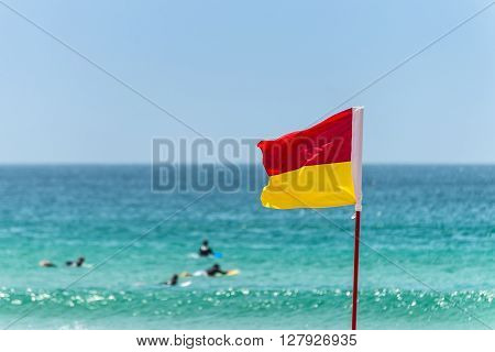 Red and yellow flag marking the limit of the safe swimming area on a beach under a blue summer sky