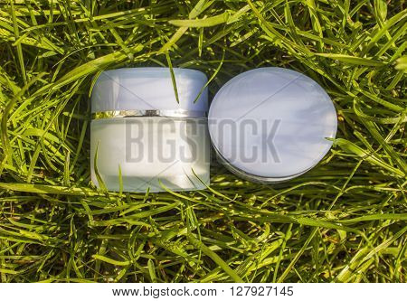 Jar with a cream on a background of green grass. Natural cosmetic.