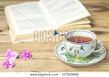 Tea cup the book and flowers on the wooden table. Shallow DOF