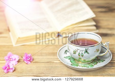 Tea cup the book and flowers on the wooden table. Image with light effects toning. Shallow DOF