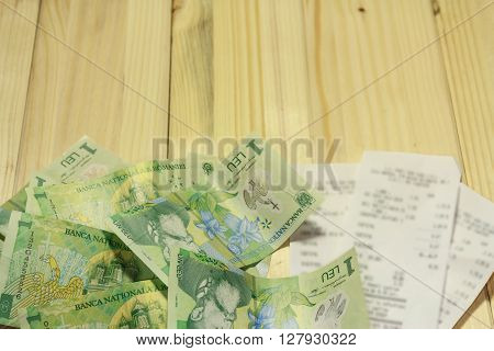 A few romanian LEU next to some grocery receipts on a wooden table ** Note: Shallow depth of field