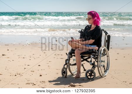 Disabled woman using mobile phone at the beach on a bright day