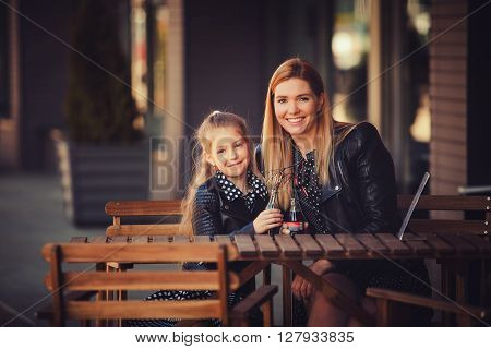 happy family sitting in the cafe. portrait of mother and daughter with a drink