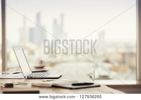 Sideview of office desktop with blank laptop and various office tools on blurry Moscow city background