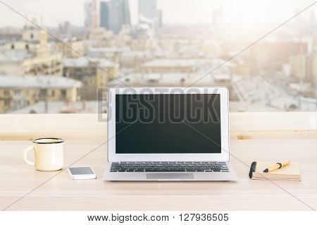 Desktop with blank black laptop iron mug and other items on blurry sunlit city background. Mock up