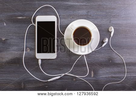 Topview of dark wooden desktop with coffee cup and saucer blank cellphone and headphones. Mock up