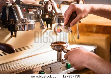 Supply of coffee. Close up of hands of pleasant professional barista using coffee machine while going to make a beverage