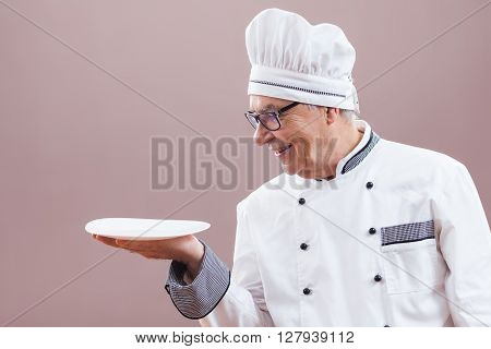 Portrait of restaurant's chef in working uniform with empty plate in his hand.