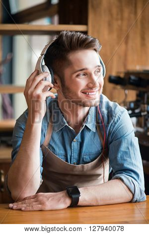 Deserve some rest . Cheerful content handsome waiter smiling at the counter an listening to music while resting at work