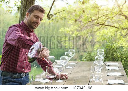 wine taster and wine glasses on a wooden table outdoor in the countryside