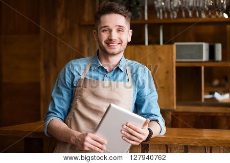 Nice beginning of the day. Pleasant cheerful handsome waiter standing near the counter and  smiling while using tablet