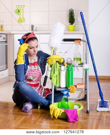 Unhappy Woman With Cleaning Supplies In The Kitchen