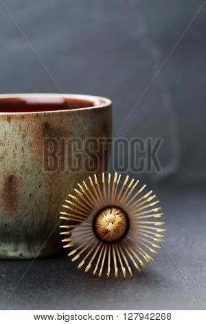 Ceramics bowl and chasen - special bamboo matcha tea whisk, lying on black stone background