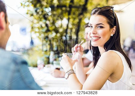Beautiful young woman sitting at a table outdoors and drinking a beverage