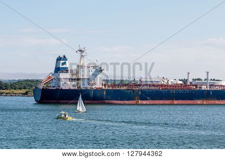 Sailboats cruising near a massive tanker in harbor