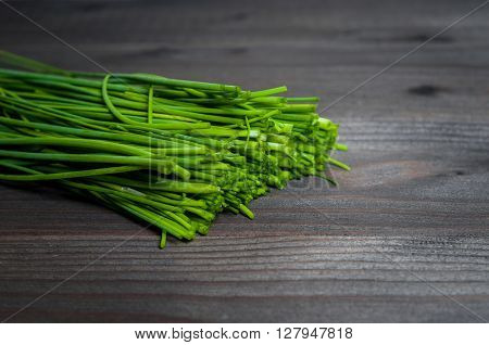 Green onions on a black wooden background. Onions on old wood. Fresh onion. Green onion. Food and health concept. Bunch of fresh green onions