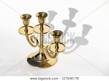 Golden candlestick on a white background with shadows close-up