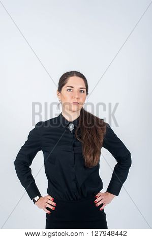 Business woman stands in strict black shirt resting his hands on her hips. Vertical photo on white background