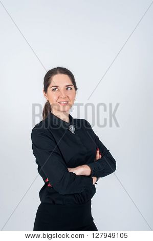 Business woman standing sideways simply in a black shirt and folded his arms on his chest and smiling looking to the side