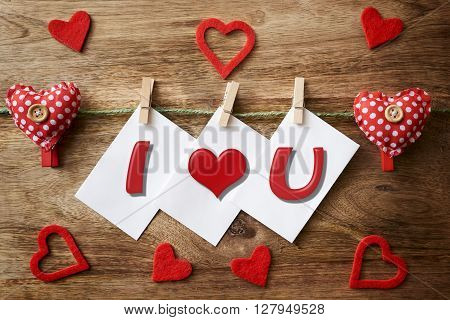 cord with cloth heart, clothespins and three paper with i love you written on wood
