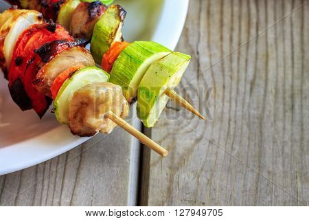 Grilled chicken and vegetables on wooden skewers on wooden background. Copy space