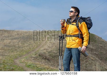 Man Holding Thermos With Hot Tea Outdoors. Hiking And Leisure
