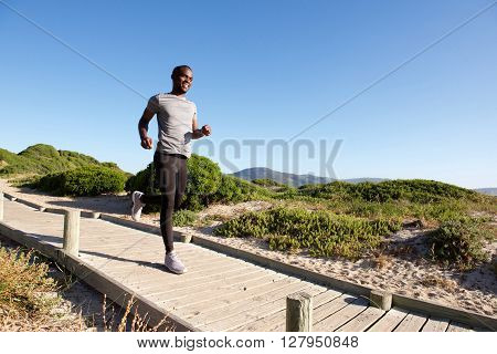 Healthy Young African Man Running On Boardwalk At The Beach