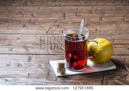 Glass mug of tea and spoon with lemon on vintage table