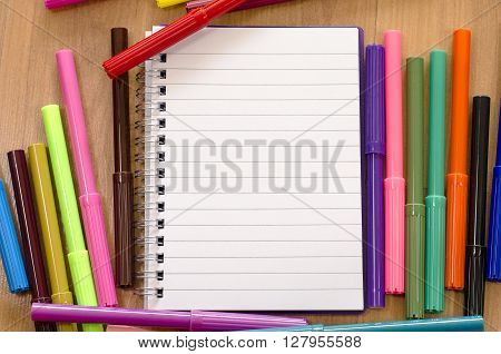Felt-tip pen and notepad on a wooden background