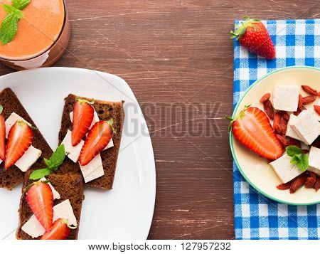 Vegan breakfast on wooden table - rye bread slices with tofu cheese and strawberries, strawberry and goji smoothie with tofu. Copy space