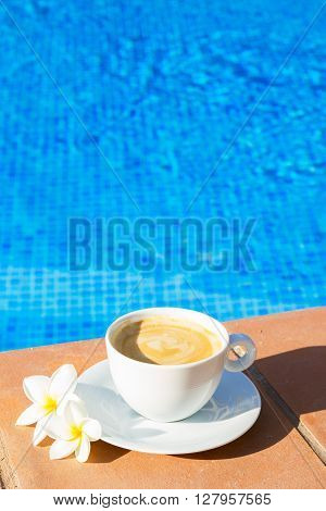 white cup of coffee near pool blue water