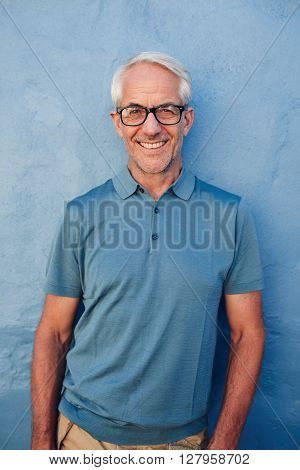 Portrait of handsome mature man with glasses looking at camera and smiling he is leaning to against a blue wall.