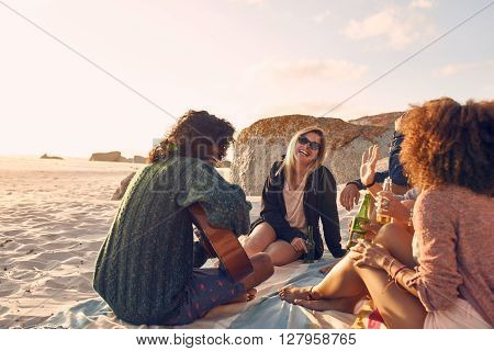 Portrait of young man playing guitar for friends. Group of friends having fun at the beach party. Young men and women sitting on the beach dinking beer.