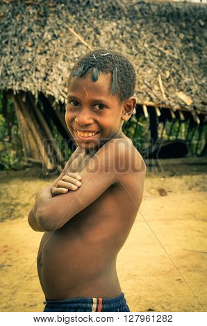 Will-will Papua New Guinea - July 2015: Young half-naked boy with crossed arms and with black feathers on his head smiles nicely to photocamera in Will-will Nuku Papua New Guinea. Documentary editorial.