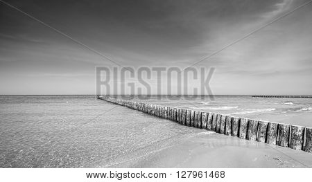 Black And White Photo Of A Wooden Breakwater On A Beach.