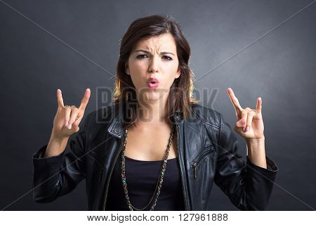 Portrait of a brunette wearing a leather jacket showing rock and roll sign