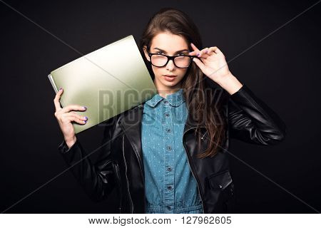 Beautiful young woman. Girl in blue overalls, wearing glasses and a leather jacket. Woman with folders. Sexy girl. High resolution photo. Hd images. Big size. Toned image