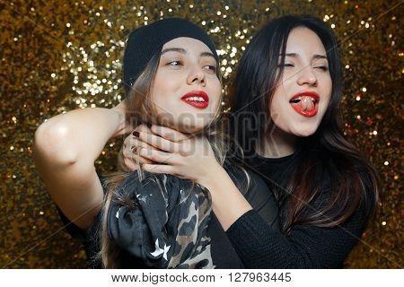 two women dressed black lesbian girlfriends having fun in night clubs photographed on gold background one girl wearing red knit cap and another black scarf with stars them red lipstick and they are very funny and passionate love each other