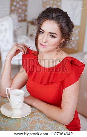 Beautiful woman drinking coffee in the kitchen.