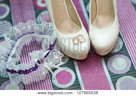 still life with wedding bride shoes and garter and gold rings.